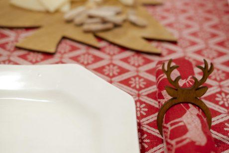 Una_pagina_en_blanco_-Arce_Rojo-Navidad-servilletero madera ciervo con plato centro al fondo de pino con quesos y mantel rojo
